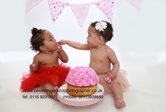 Twin sisters enjoying a cake smash photo session